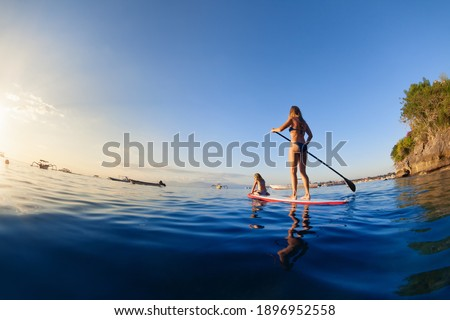 Active paddle boarder at sunset sea. Young mother with little clild paddling on stand up paddleboard. Healthy lifestyle. Water sport, SUP surfing tour in adventure camp on family summer beach vacation Stock photo ©