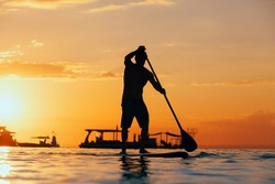 Active paddle boarder. Black sunset silhouette of young sportsman paddling on stand up paddleboard. Healthy lifestyle. Water sport, SUP surfing tour in adventure camp on family summer beach vacation.