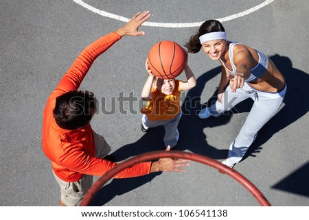 Active parents teaching their son how to play basketball
