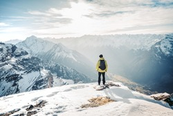 Active people in nature concept. Dressed bright yellow jacket male backpacker enjoying the view as she have mountain walk.Tourist with a backpack and mountain panorama. Adventure concept