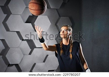 Active playing girl with a basketball on cell gray background