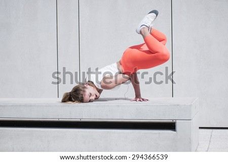 Active Pretty Young Female Dancer Doing a Hip Hop Dance Pose on White Bench