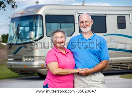 Active retired couple in love with their luxury motor home in background.