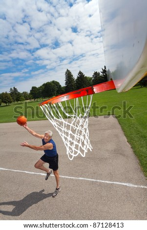 Active retired man shoots hoops outdoors. His dynamic shadow is cast on the court. Background of grass, trees, blue sky, fluffy clouds.  Wide angle looking down from the net. Copy space provided.