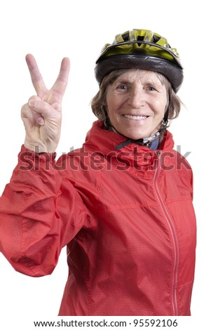active retired woman wearing bicycle helmet and red windbreaker jacket showing peace sign with fingers