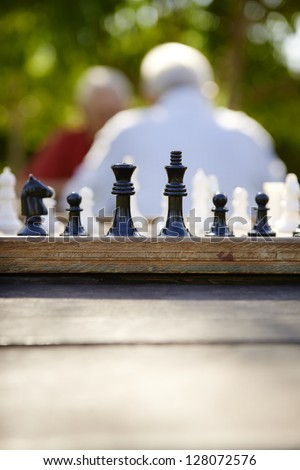 Active retirement, old friends and leisure, two senior men having fun and playing chess game at park. Focus on chessboard in foreground