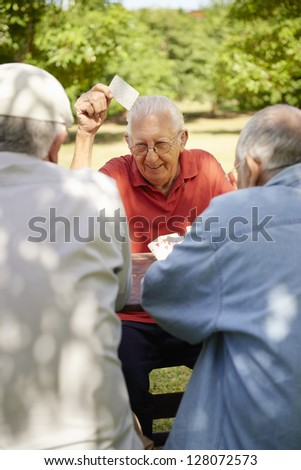 Active Retirement, Old People And Seniors Free Time, Group Of Three Elderly Men Having Fun And Playing Cards Game At Park. Waist Up