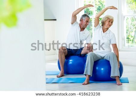 Active senior couple doing aerobics on ball at home