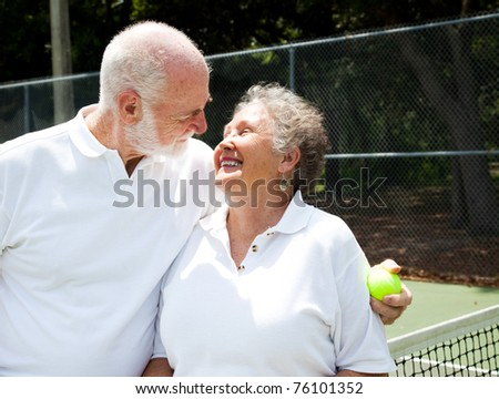 Active senior couple gets romantic on the tennis courts.