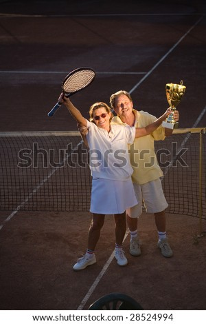 Active senior couple is posing on the tennis court with tennis racket and cup in hand. Outdoor, sunlight.