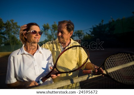 Active senior couple is posing on the tennis court with tennis racket in hand. Outdoor, sunlight. - stock photo
