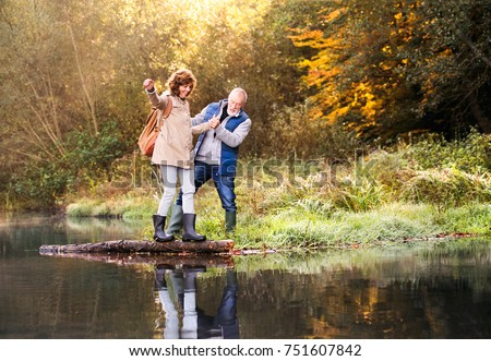 Active senior couple on a walk in a beautiful autumn nature. A woman and man by the lake in the early morning.