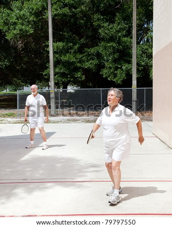 Active senior couple playing racquetball at the park.
