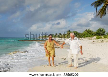 Active senior couple walking on the beach, getting wet, enjoying retirement on tropical destination: Maria la Gorda on caribbean island Cuba
