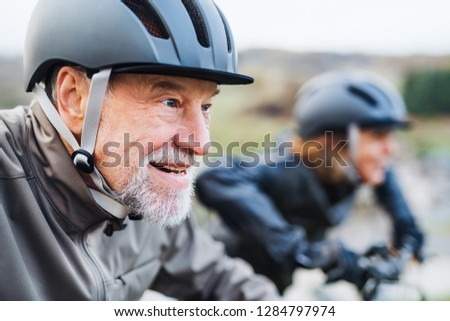 Active senior couple with electrobikes cycling outdoors on a road in nature. #1284797974