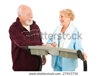 Active senior couple working out at the gym.  Isolated on white.