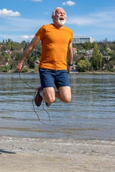 Active senior elderly man jumping the rope, exercising on the beach by the riverbank. Motion blur.