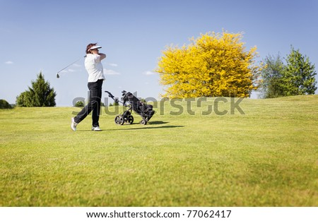 Active senior female golf player swinging golf club to shoot ball on fairway on beautiful golf course with blue sky in background.