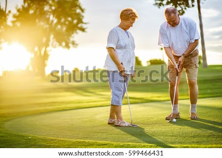 active senior lifestyle, elderly couple playing golf together at sunset