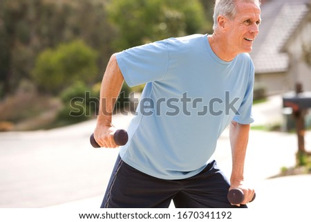 Active senior man exercising with dumbbells outdoors