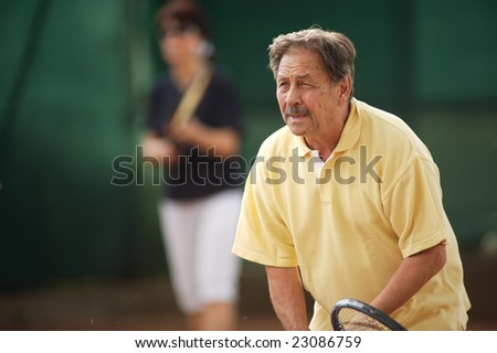Active senior man in his 70s playing tennis.