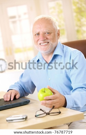 Active senior man sitting at desk at home, smiling, holding apple.?
