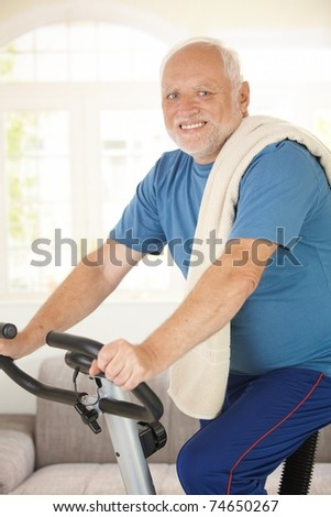 Active senior using exercise bike at home, smiling at camera.?