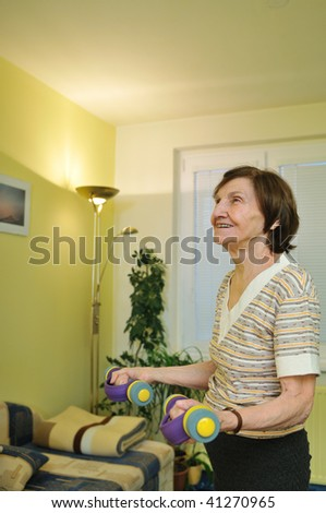 Active senior woman exercising at home with barbells