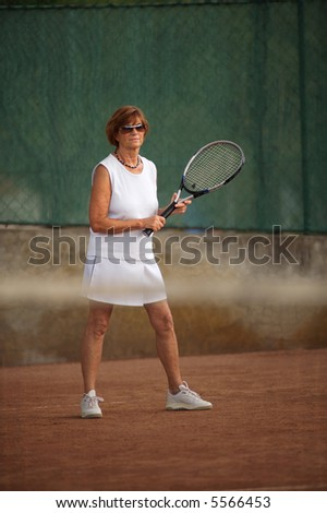 Active senior woman in her 60s plays tennis. - stock photo