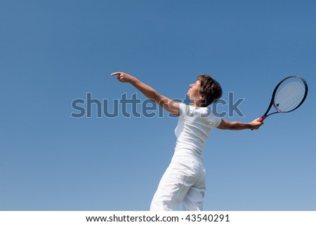 Active senior woman is playing tennis in front of blue sky