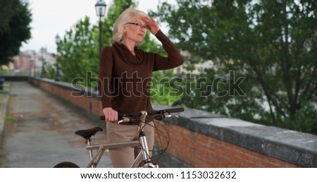 Active senior woman on bike ride stops to admire view in the city #1153032632