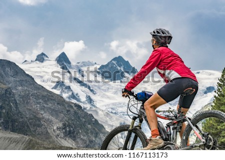 active senior woman, riding her e-mountain bike in the Roseg valley below the glaciers and summits of the Sella Group and Piz Roseg #1167113173