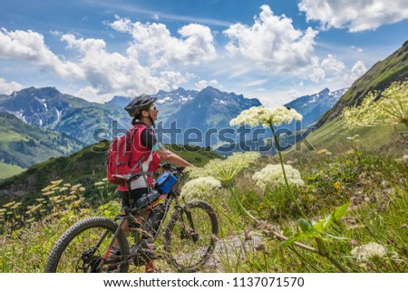 active senior woman, riding her e-mountainbike in the Arlberg area near the famous village of Lech, Tirol, Austrian Alps