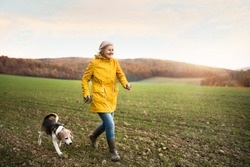 Active senior woman with dog on a walk in a beautiful autumn nature.