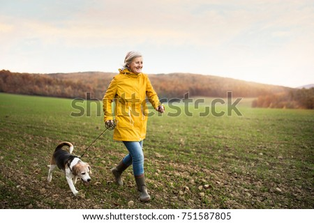 Active senior woman with dog on a walk in a beautiful autumn nature. #751587805