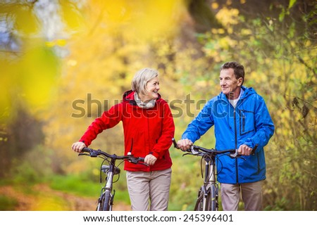 Active seniors having walk with bike in autumn nature. They having romantic time outdoor. #245396401