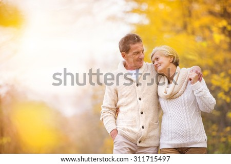 Active seniors on a walk in autumn forest