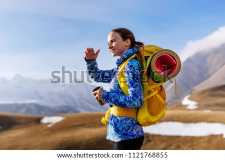 active smiling girl in a blue jacket travels through the Caucasus mountains with a backpack