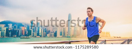 Active sport runner man jogging in Hong Kong city street living a healthy lifestyle training morning workout. Caucasian expat male athlete working out cardio banner panorama. #1175289580