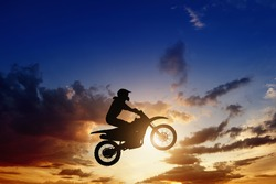 Active sports background - jumping motorcycle rider silhouette, beautiful sunset