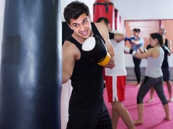 active sportsman in the boxing hall practicing boxing punches with boxing bag during training