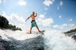 active sporty attractive male wakesurfer balancing on board on river wave against in background blue sky