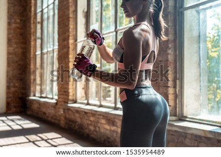 Active sporty fit young beautiful toned woman in sportswear holding bottle of water in loft gym studio indoors, healthy athlete girl drinking water during sport workout fitness training lifestyle
