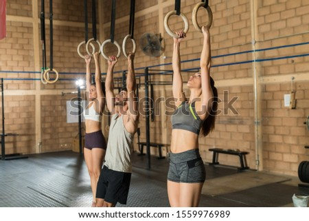 Active sporty friends working out while hanging from gymnastic rings at health club