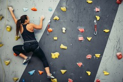 Active sporty woman practicing rock climbing on artificial rock in climbing s. Extreme sports and bouldering concept.