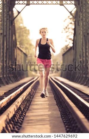 Active sporty woman running on railroad tracks bridge during morning endurance training run.