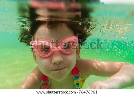 Active underwater kid in sea. Girl swims and having fun. Child sport on summer vacation