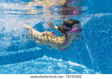 Active underwater kid in swimming pool. Girl swims and having fun. Child sport on summer vacation