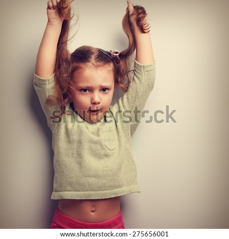 Active unhappy emotion kid girl pulling her long hair up. Vintage closeup portrait
