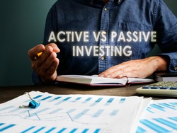 Active vs passive investing concept. The investor is sitting at the table.